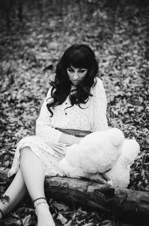 psychics: Young sad lonely brunette girl at sleepwear sitting on autumn forest and read book near soft toy bear. Black and white photo. Stock Photo