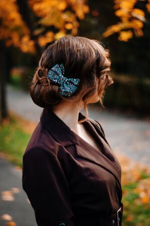 Portrait of smart girl with old-fashioned hairstyle outdoor in brown coat on autumn. Bow on hair. Stock Photo