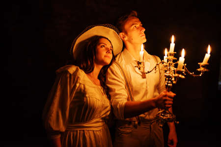 dark cave: Handsome old fashioned retro couple with burning candles on candlestick at dark cave.