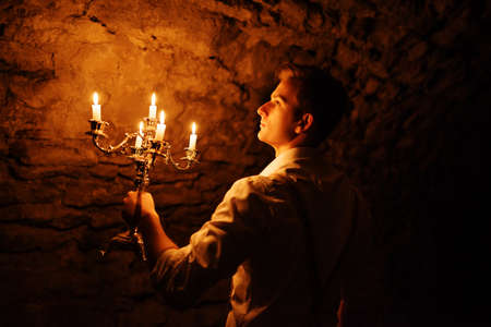 dark cave: Handsome old fashioned retro boy with burning candles on candlestick at dark cave.