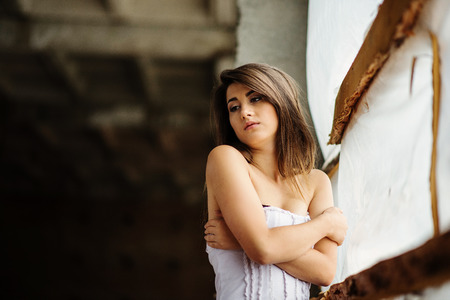 Close up portrait of young cute brunette girl posed on abandoned place. Stock Photo