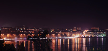 Panorama of night city lights and reflections on lake at Ternopil, Ukraine, Europe.