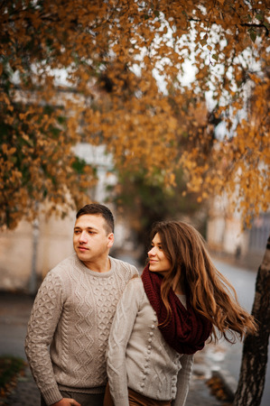 Young couple wearing on tied warm sweaters hugging in love at city in autumn.