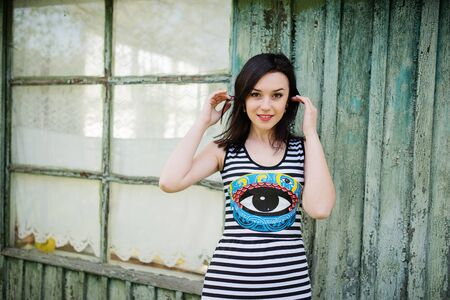 cian: Brunette model girl at dress with stripes background cian wooden house with old windows. Stock Photo