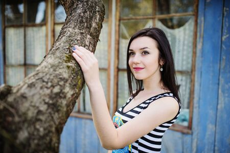 Brunette model girl at dress with stripes posed near tree. Stock Photo