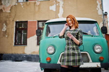 turqoise: Young red haired girl lady with mobile cell phone and headphones, wearing on checked dress background old vintage turqoise minivan bus. Stock Photo