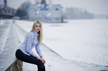 Portrait of young cute blonde girl on blouse at pier background foggy river on winter ice.