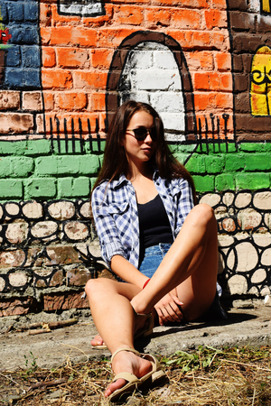 Portrait of beautiful teenage girl in sunglasses weared on checkered shirt and jeans shorts, against a wall with some element of graffiti.