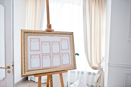 Wedding seating chart on the easel at light restaurant.