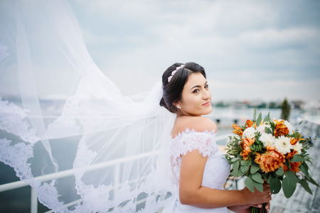Brunette bride stay on the pier berth at cloudy day.