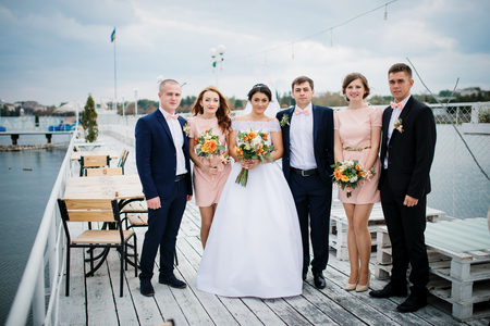 embracement: Wedding couple with bridesmaids and best mans stay on the pier berth at cloudy day. Stock Photo