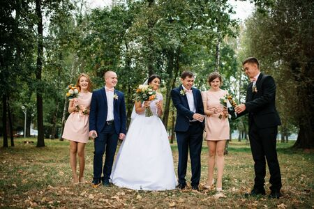 embracement: Wedding couple with bridesmaids and best mans drink champagne at park.