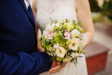Close up wedding bouquet at hands newlyweds.