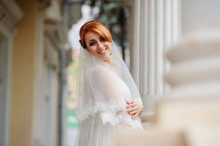 smiled: Smiled red haired bride background large columns of antique house.