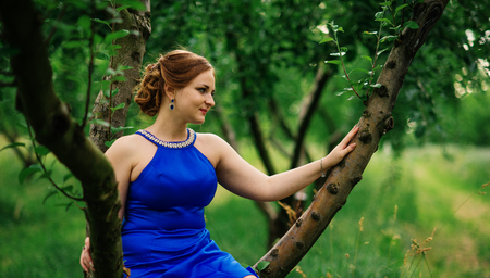Young overweight girl at blue dress posed background spring garden sitting on tree. Stock Photo