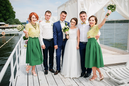 man's: Wedding couple with bridesmaids and best mans at pier.