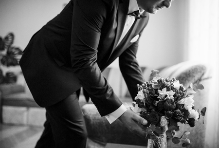 cuff: Groom with wedding bouquet at his room at morning day. Black and white photo