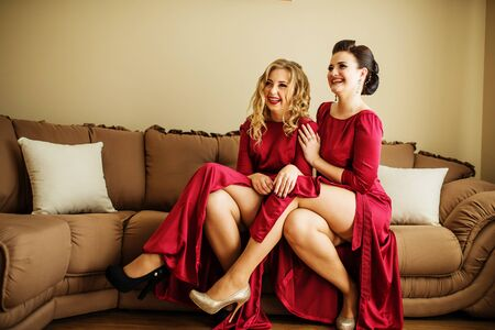 Two sexy bridesmaids showing her legs from red dresses at wedding day. Stock Photo