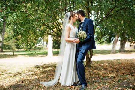 Wedding couple stay under tree at green park.