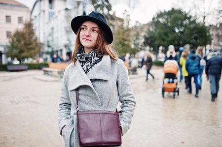 Young model tourist girl in a gray coat and black hat with leather handbag on shoulders posed at street of city.