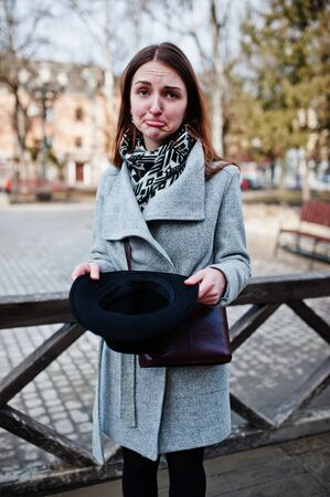 Tourist have not money concept. Sad face. Young model girl in gray coat and black hat with leather handbag on shoulders posed against wooden beams at street of city. Stock Photo
