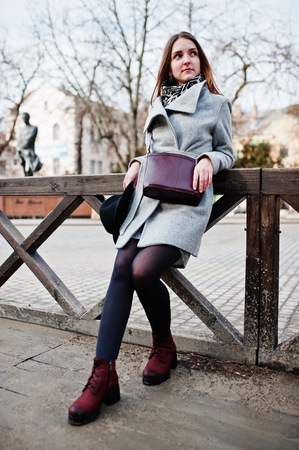 Young model girl in gray coat and black hat with leather handbag on shoulders posed against wooden beams at street of city.