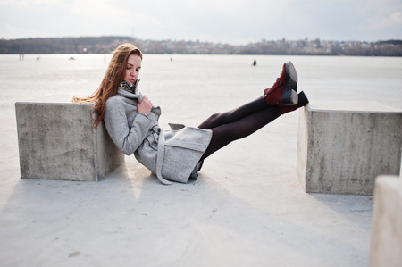 Young model girl in gray coat posed sitting near stone cube against freeze lake.