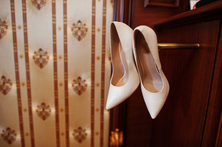 luxury hotel room: Beige luxury wedding shoes at wooden cabinet on hotel room. Stock Photo