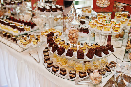 Different types of cakes and baking at wedding reception table.