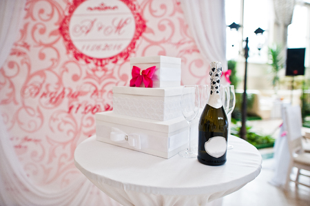 Small table with box for money and champagne at wedding ceremony.