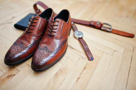 Accessories for mens lay on the wooden parquet floor.