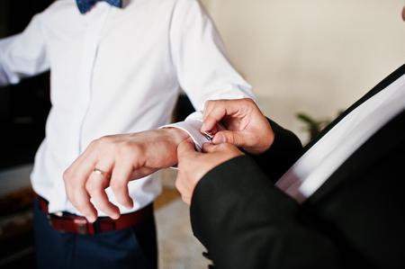 cuff link: Best man helped stylish groom wear cuff links at wedding day. Stock Photo