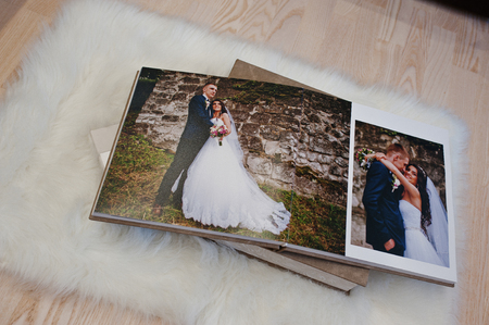 Pages of wedding photobook or wedding album at carpet on wooden background.
