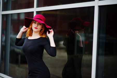 Portrait of fashion red haired girl on red hat and black dress with bright make up posed against large window. Stock Photo