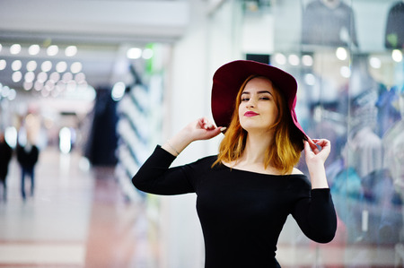 Fashion red haired girl wear on black dress and red hat posed at trade shopping center. Stock Photo
