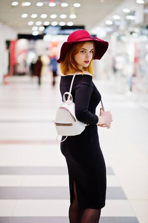 Fashion red haired girl wear on black dress and red hat with ladies backpack posed at trade shopping center. Photo toned style Instagram filters.