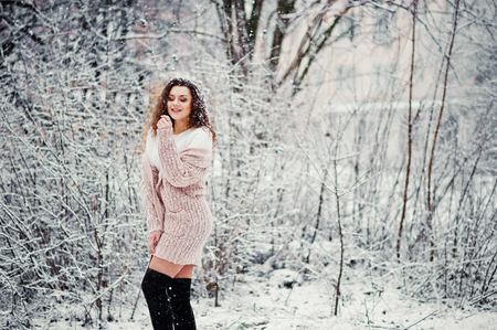 Curly brunette girl background falling snow, wear on warm knitted sweater, black mini skirt and wool stockings.