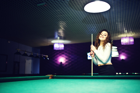 Young curly girl posed near billiard table. Sexy model at black mini skirt play russian snooker. Play game and fun concept. Stock Photo