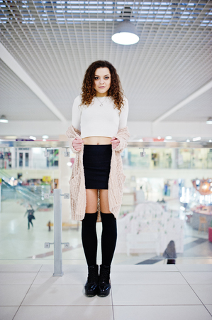 entertainment center: Young curly model girl posed on mini skirt at large shopping center near glass railings.