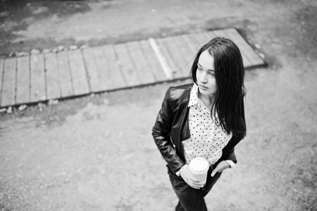 Portrait of stylish young girl wear on leather jacket and ripped jeans with cup of coffee. Street fashion model style. Black and white photo.