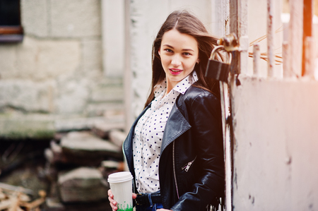 Portrait of stylish young girl wear on leather jacket and ripped jeans with cup of coffee. Street fashion model style.