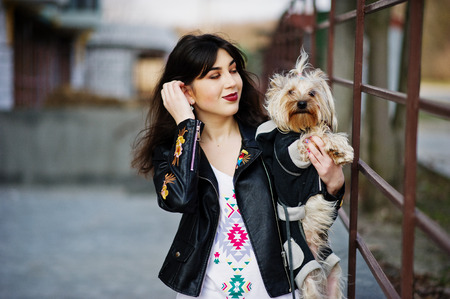 Brunette gypsy girl with yorkshire terrier dog posed against steel railings. Model wear on leather jacket and t-shirt with ornament, pants.