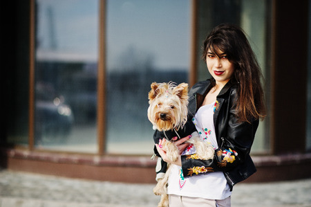 Brunette gypsy girl with yorkshire terrier dog posed against large windows house. Model wear on leather jacket and t-shirt with ornament, pants.