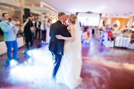 Amazing first wedding dance with fog smoke at dancefloor and various lights. Stock Photo