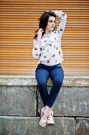 Young stylish brunette girl on shirt, pants and high heels shoes, sitting and posed background orange shutter. Street fashion model concept.