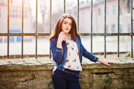 Young stylish brunette girl on shirt, pants, jeans jacket  posed background iron fence. Street fashion model concept. Stock Photo