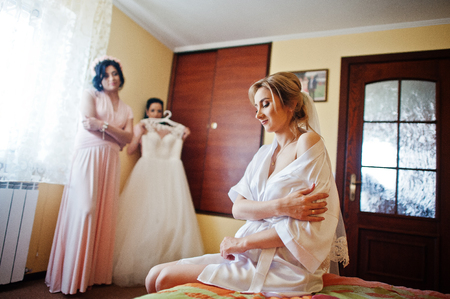 Bride on silk robe against bridesmaids with her wedding dress, siiting on bed at room on morning day.