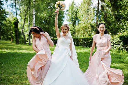 Bride posed on park with two cute brunette bridesmaids on pink dresses.