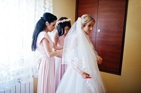 Las damas de honor de moda en vestidos rosados ??ayudaron a usar el arco en la parte posterior de la novia del vestido de novia. Día de la boda de mañana