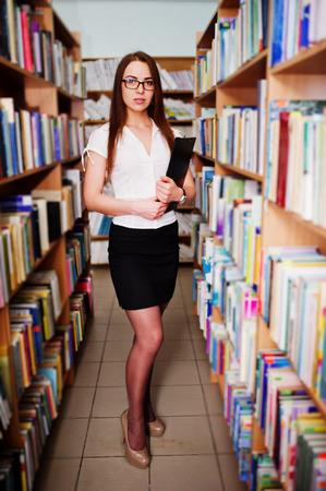 白いブラウスと黒いミニのスカートでブルネットの少女、ドキュメントのフォルダーとライブラリでメガネを着用します。セクシーなビジネス女性